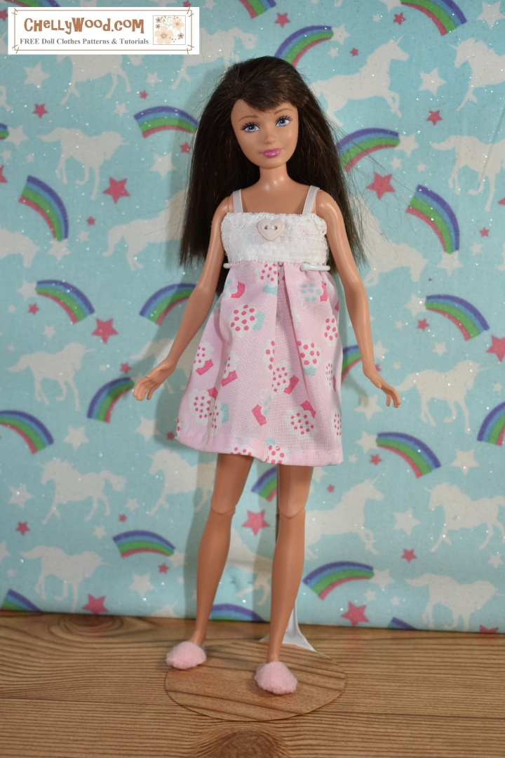 Mattel's Skipper is shown wearing a cotton Babydoll pajama top with shorts, but the shorts cannot be seen as the camera angle is above her head a bit. The pajama uses lace and a heart-shaped button. She also wears felt slippers. The cotton pajama is decorated with cupcakes. Behind her is a wall that appears to be decorated with unicorns, rainbows, stars, and glitter... themes reminiscent of the dreamscape. The overlay, ChellyWood.com, is the URL for a website where you can find the free, printable sewing patterns for making this  pajama set for Barbie, Skipper, Francie, and similar-sized dolls.