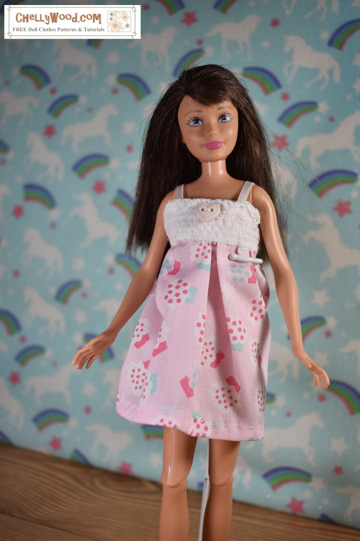 The image shows Mattel's 10 inch Skipper doll wearing a pink pajama with a heart-shaped button on the bodice. It has lace straps and the pink gathered fabric is topped with a lace bodice. The fabric is decorated with cupcakes. If you want to make this pajama set for Skipper, the free printable sewing pattern is available at ChellyWood.com (the watermark overlaid on this image).