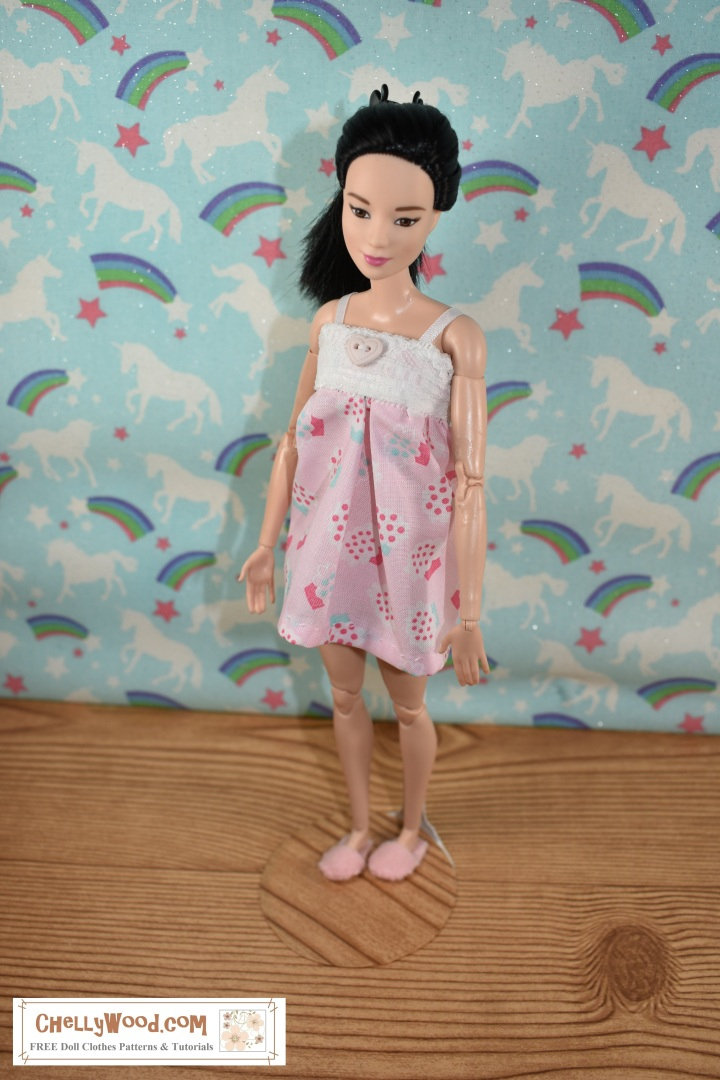 Made to Move Barbie is wearing a cotton Babydoll pajama top with shorts, but the shorts cannot be seen as the camera angle is above her head a bit. The pajama uses lace and a heart-shaped button. She also wears felt slippers. The cotton pajama is decorated with cupcakes. Behind her is a wall that appears to be decorated with unicorns, rainbows, stars, and glitter... themes reminiscent of the dreamscape. The overlay, ChellyWood.com, is the URL for a website where you can find the free, printable sewing patterns for making this  pajama set for Barbie and similar-sized dolls.