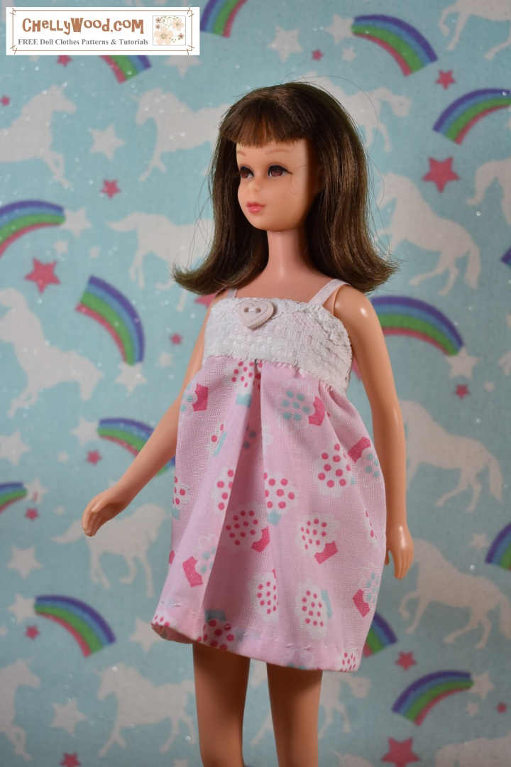 A vintage Francie doll from Mattel is shown wearing a cotton Babydoll pajama top with shorts, but the shorts cannot be seen as the camera angle is above her head a bit. The pajama uses lace and a heart-shaped button. She also wears felt slippers. The cotton pajama is decorated with cupcakes. Behind her is a wall that appears to be decorated with unicorns, rainbows, stars, and glitter... themes reminiscent of the dreamscape. The overlay, ChellyWood.com, is the URL for a website where you can find the free, printable sewing patterns for making this  pajama set for Barbie, Skipper, Francie, and similar-sized dolls.
