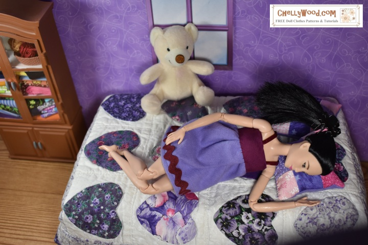 """The image shows a Made-to-Move Barbie wearing a handmade babydoll pajama. The doll's lilac-colored pajamas are trimmed in bias tape, ribbon, and rick-rack. Barbie lays on a doll-sized bed with a small quilt on the bed. The quilt has little hearts on it (for this image was posted in February, for Valentine's Day. Barbie's head lays on a quilted pink-and-purple nine patch pillow. She has a stuffed bear on her bed and a cabinet in the background. The wallpaper is purple and there's a window in the wall behind her. The whole diorama is 1:6 scale to suit Barbie. The doll wraps her hand around the nine-patch quilted doll pillow, and she has her legs crossed at the ankle as she reclines upon her little quilt-covered bed. The overlay offers the website where you can find free patterns for making the Barbie doll pajamas and a pair of shorts that cannot be seen in this image, but which go with the baby doll pajamas. The overlay says: ChellyWood.com and it also says, """"Free doll clothes patterns and tutorials"""" -- this website offers free doll clothes patterns for dolls of many shapes and sizes. Each pattern comes with a free tutorial video showing you how to make the clothes."""