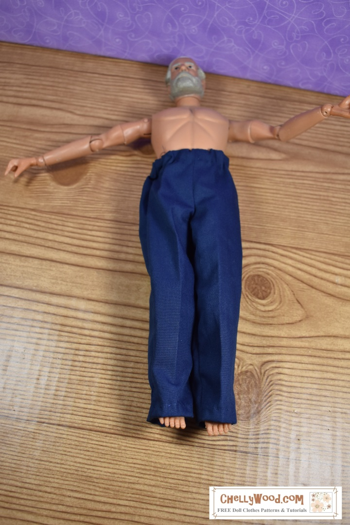 The image shows a Civil War GI Joe doll with beard wearing a pair of hand-made navy blue slacks or trousers. These pants were made using free doll clothes patterns found at ChellyWood.com. The trousers or pants appear to be about 1 cm too long for the doll / action figure.