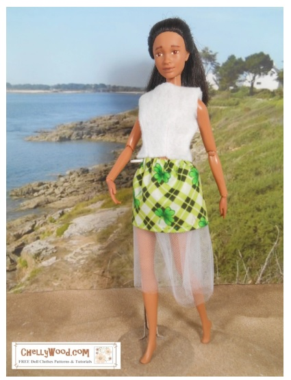 The image shows a Mattel Barbie doll wearing a handmade skirt with tulle. The fabric uses a shamrock plaid pattern for St. Patrick's day.