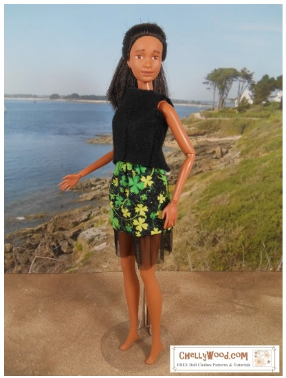 The image shows Mattel Barbie doll wearing a handmade skirt with shamrocks all over the fabric. Under the skirt is opaque black tulle to give the skirt's base a wispy look.