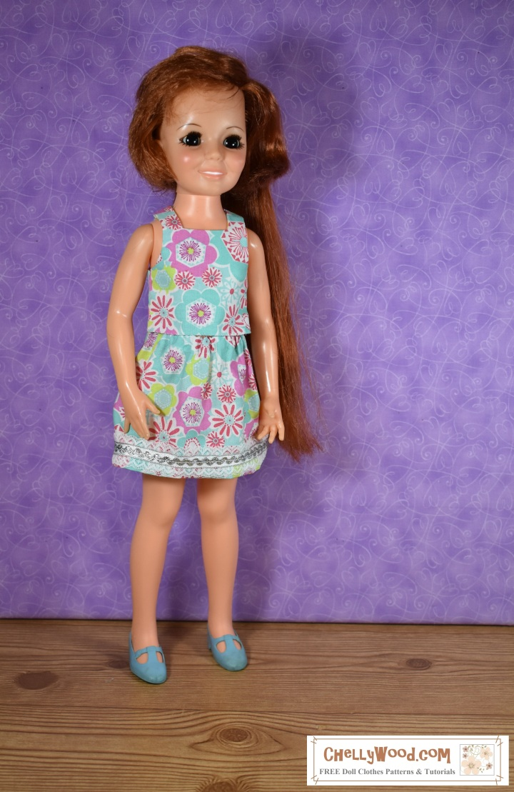The image shows a Crissy doll from Ideal Toy Corporation wearing a 1970's outfit including a floral skirt and floral top in bright colors that are retro and reminiscent of the 1970 era. She also wears MaryJane shoes. The overlay says ChellyWood.com: free patterns and tutorials.