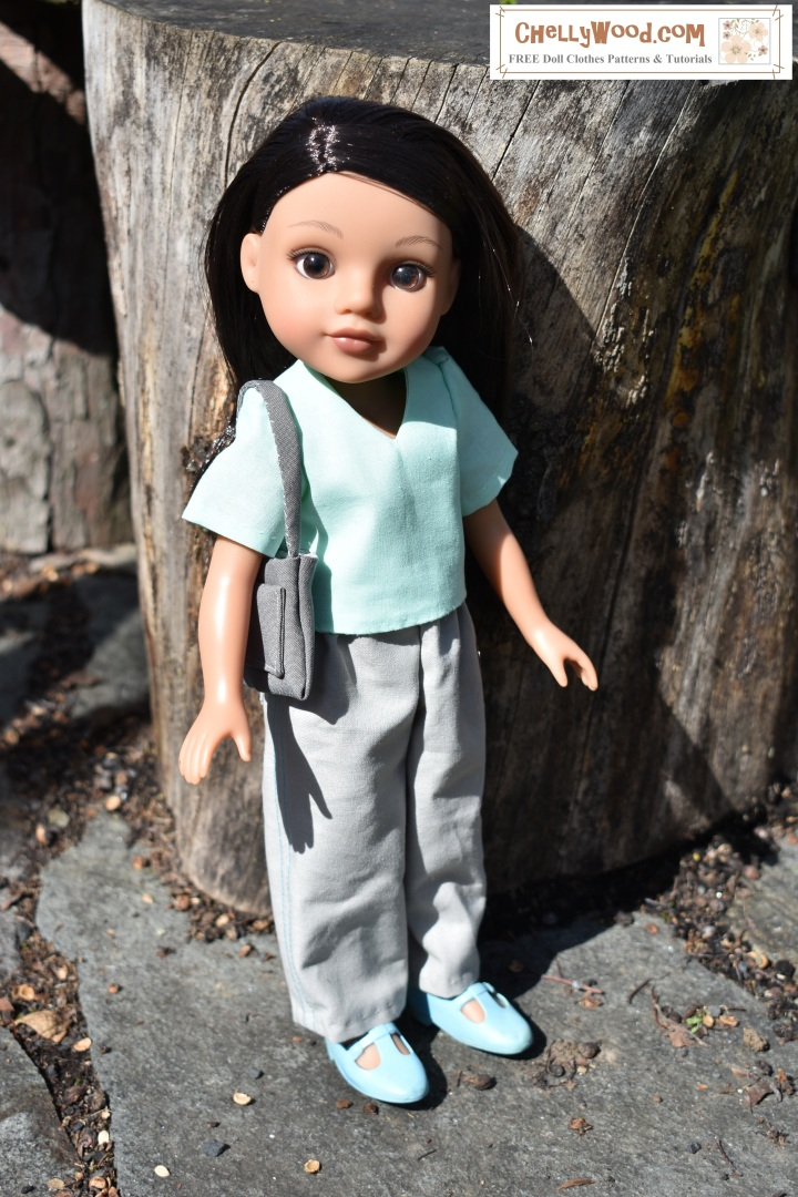 The image shows Consuelo, the Hearts4Hearts Girl doll wearing handmade clothes including a shirt, pants with a pocket, and a purse with a side pocket. She stands in front of a stump, and she has plastic Mary Jane style shoes on her feet. The color of the shoes match the color of her short-sleeve, V-neck shirt. The color of the purse is akin to the khaki-grey color of the pants she wears. In the corner of the image is a watermark stating where you can find free printable sewing patterns for making this outfit: ChellyWood.com