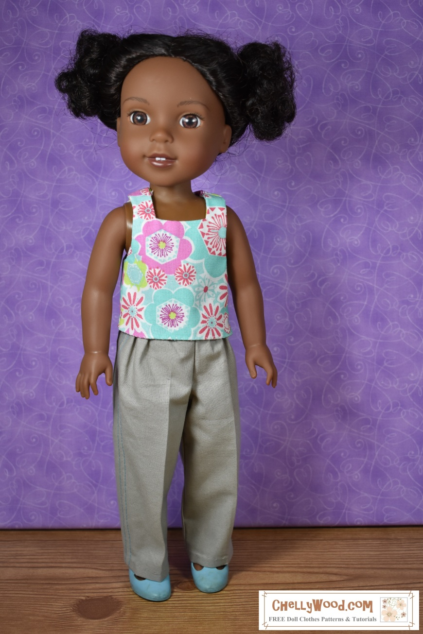 "The image shows a Wellie Wisher doll (Kendall from American Girl) wearing a handmade square-neck tank top and khaki pants. Her plastic shoes are MaryJanes. At the bottom of the image, there's a URL for the website where you can print the free pattern for making this entire outfit: ChellyWood.com. The Chelly Wood website's motto is ""free doll clothes patterns and tutorials for dolls of many shapes and sizes."" Patterns are offered as a PDF download and a MS Word document, for easy printing."