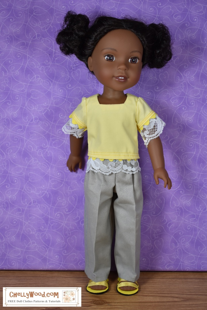 """The image shows a Wellie Wisher doll (Kendall from American Girl) wearing a handmade square-neck short sleeve blouse with lace at the sleeves and waist and khaki pants. Her handmade shoes are sandals made of craft foam and ribbon. At the bottom of the image, there's a URL for the website where you can print the free pattern for making this entire outfit: ChellyWood.com. The Chelly Wood website's motto is """"free doll clothes patterns and tutorials for dolls of many shapes and sizes."""" Patterns are offered as a PDF download and a MS Word document, for easy printing."""