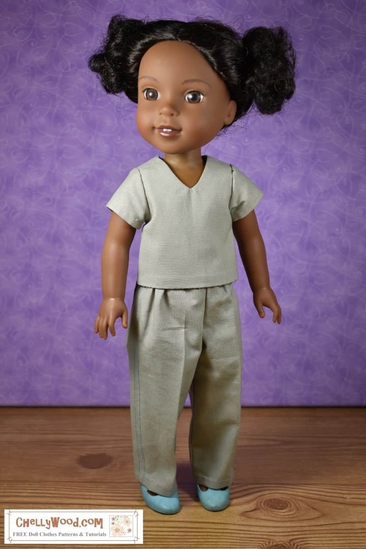 "The image shows American Girl Wellie Wisher doll Kendall wearing a pair of pants and shirt that resemble medical scrubs. The overlay says, ""ChellyWood.com: FREE doll clothes patterns and tutorials"" and in fact, the website does offer a free prinable pdf pattern of these pants and this shirt to fit 14 inch or 15 inch dolls."