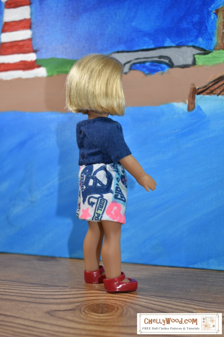"The image is a side view of the 6 and a half inch American Girl doll named ""Kit Kittredge"" wearing handmade doll clothes including a navy blue tee shirt and a pair of jersey-fabric shorts to match in a colorful navy and pink print with ""girl power"" words printed on the jersey fabric. The watermark says ""ChellyWood.com"" which is a website where you can find lots of free printable sewing patterns for dolls of many shapes and sizes, including free patterns for the 6 inch AG dolls."