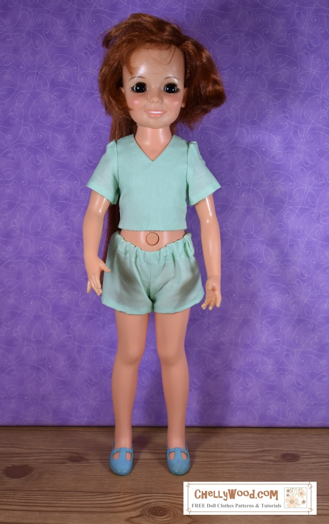 The image shows a vintage Crissy doll from Ideal Toy Corp wearing a handmade V-neck shirt with matching shorts. This image is part of a #memade Monday post on the doll clothes sewing patterns website ChellyWood.com, where you can download free printable pdf patterns to fit Crissy dolls, American Girl dolls, Wellie Wisher dolls, Barbie dolls, Monster High dolls, and many other dolls of different shapes and sizes.