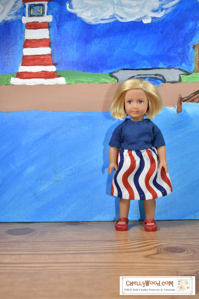 This photograph shows the six inch American Girl Mini doll Kit Kittredge standing on a boardwalk with a seascape in the backdrop. There's a lighthouse in the distance, along with a sand bank and a dock. The doll wears tiny red Mary Jane shoes, a handmade navy blue T-shirt, and a hand-sewn skirt that's patterned with red, white, and blue wavy stripes. The watermark in the corner of the photo tells the website where you can download the free printable pdf sewing pattern for making this outfit for 6-inch American Girl Mini dolls: ChellyWood.com