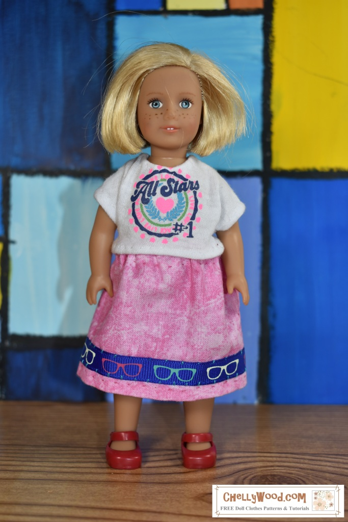 """The image shows a 6"""" Mini American Girl doll wearing a handmade tee shirt and a handmade skirt. You can download the free printable PDF sewing pattern for making this outfit at ChellyWood.com."""