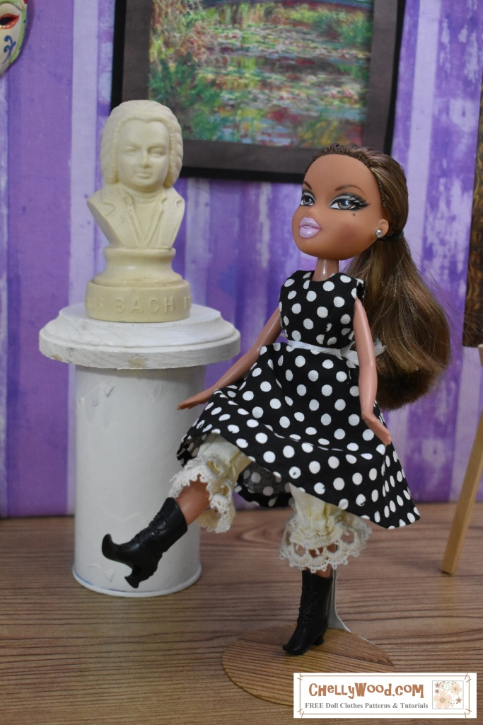 This is a photo of a Bratz doll kicking up her heels to show off her cute lace-trimmed bloomers under her black and white polka dot A-line dress. The doll appears to be dancing through an art museum, with a bust of Bach behind her and a Monet garden painting on the wall of the museum behind her. The watermark tells where you can find this and other free printable sewing patterns for doll clothes that fit the Bratz line of dolls: ChellyWood.com