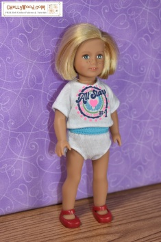 The image shows the American Girl Mini 6-inch doll modeling handmade underpants (knickers) and a hand-made graphic tee shirt. To get to the free printable PDF sewing patterns and links to tutorials, you must click on this link: https://wp.me/p1LmCj-Gk2