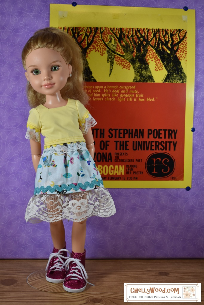 The image shows a BFC Ink doll wearing a handmade outfit which includes a lace-trimmed skirt and lace-trimmed shirt. The outfit was hand-sewn using free patterns from ChellyWood.com. The doll stands in front of a colorful retro poster that was designed by (and used with permission from ) the UA Poetry Center at the University of Arizona.