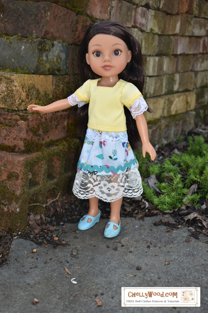 "The image shows Consuelo, one of the Hearts for Hearts Girls, wearing a handmade skirt with lace trim and a bright yellow blouse with lace trim and a ""scalloped-look"" rickrack trim around the bottom of the shirt and the edges of the sleeves of the shirt. The neckline of the shirt is square. The doll stands in an outdoor garden near a brick wall. At the bottom of the image, we see a watermark telling where you can go to download the free printable sewing patterns for making these doll clothes: ChellyWood.com"