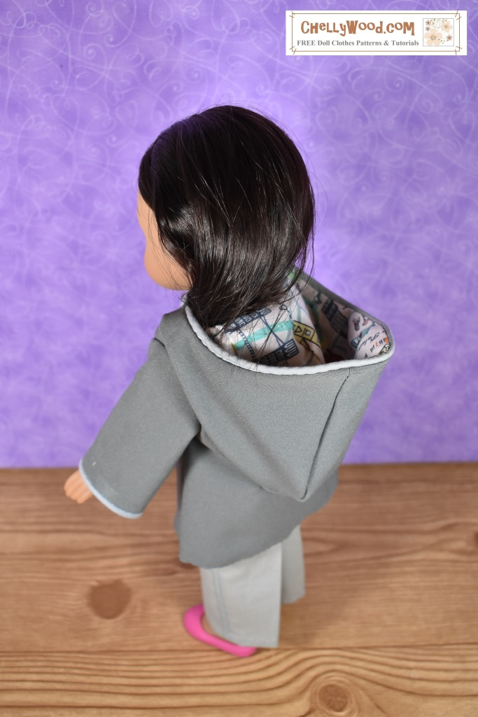 The image shows a 15-inch doll wearing a hand-made rain coat. The website where this image comes from offers free printable sewing patterns for 15-inch doll clothes. The website is called ChellyWood.com
