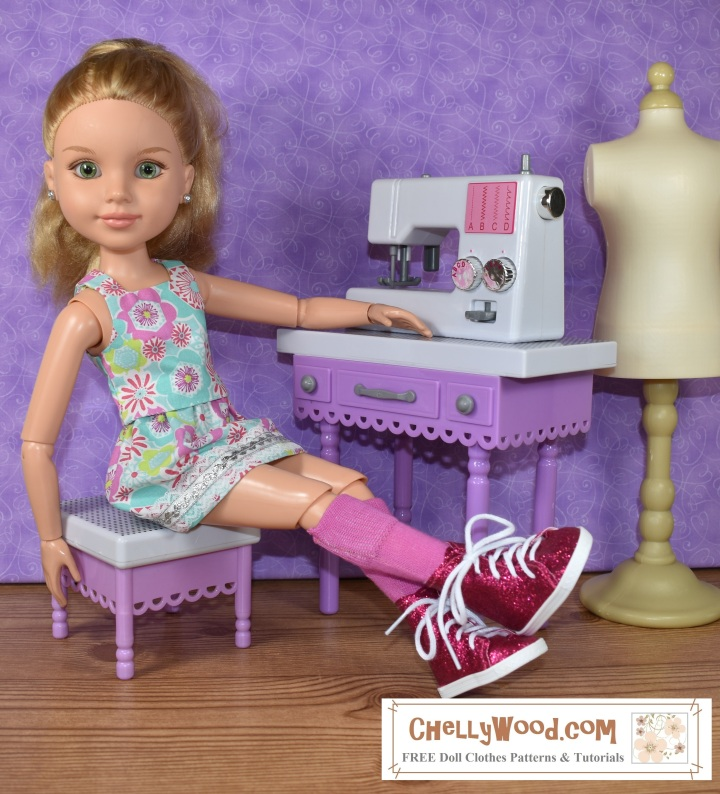 In this image, we see a blond-haired BFC Ink doll with a highly articulated body, seated at a sewing machine. She wears a blousy tank top ans matching skirt made of 1970's printed floral fabric. Her legs are crossed in front of her, and one hand rests on the sewing table beside her little miniature sewing machine. She wears high-top glittery pink sneakers and knee-high pink socks. Her expression is mildly surprised like this was a candid photo. Behind her sewing table is a dress form that looks as though it might fit 18 inch dolls. The website given in the watermark (which is where you can find free patterns and tutorials for making her skirt and top) is ChellyWood.com