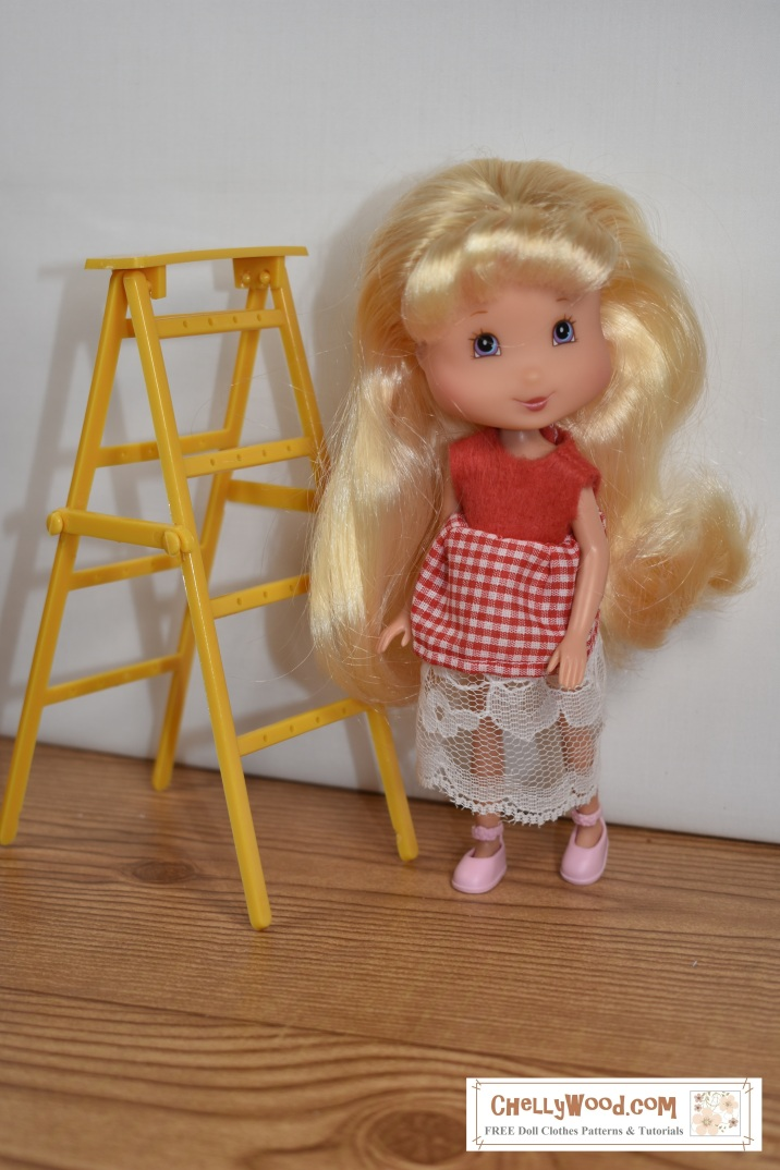 Image shows a 7-inch Strawberry Shortcake doll from the Playmates line of toys wearing a handmade doll dress made of gingham, felt, and lace. The caption offers a link to the printable free patterns and an easy sew tutorial video showing how to make this dress.