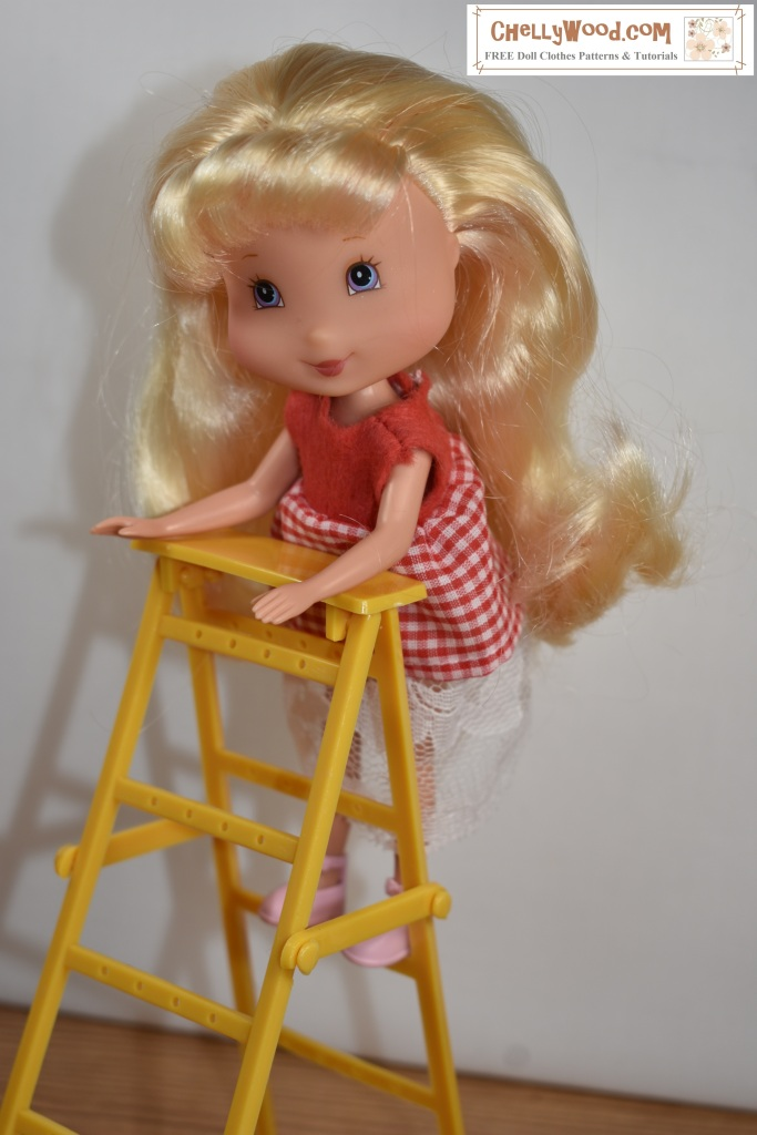 "This photo shows a Lemon Meringue doll from the Playmates' Strawberry Shortcake collection climbing a tiny ladder. The doll wears a very short gingham dress (made of gingham fabric, lace fabric, and felt). She appears to be having fun playing on the ladder, but her skirt is precariously short. The overlay says ""ChellyWood.com"" and suggests that the website is where you can find free printable PDF sewing patterns to fit 7-inch Strawberry Shortcake dolls."