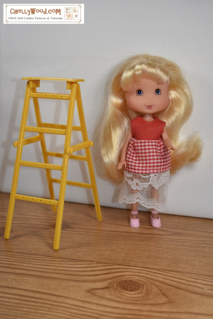In this photograph, a Lemon Meringue doll (from the Playmates Strawberry Shortcake collection of friends) stands beside a tiny yellow ladder. Her liquid-like gold hair shimmers, cascading down her shoulders and ending in curls near her fingertips. She wears a handmade dress made of felt for the bodice, gingham for the skirt, and a lace petticoat. The watermark says that ChellyWood.com offers free patterns and tutorials.