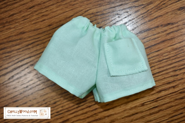 Please visit ChellyWood.com for free printable sewing patterns for dolls of many shapes and sizes. This image shows a pair of doll shorts with an elastic waist and a single pocket at the back (buttocks) area of the shorts. The image has a watermark which says where you can find the free printable sewing pattern and easy-to-follow tutorial video for making a pair of shorts like these to fit your dolls. These shorts will fit dolls in the 13-inch (33 cm), 14 inch (35.5 cm), 15 inch (38 cm), 16 inch (40.5 cm), and even some 17 inch or 18 inch (43 cm to 46 cm) size range. The website where you can find the free patterns for these shorts and instructions for making them is ChellyWood.com