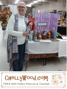 The image shows the real Chelly Wood, holding a Strawberry Shortcake doll that she has cleaned and re-done after finding it in terrible condition at her local second hand store. She stands before her booth at a craft fair in Idaho where she advertised her website, ChellyWood.com (a free doll clothes sewing pattern website).