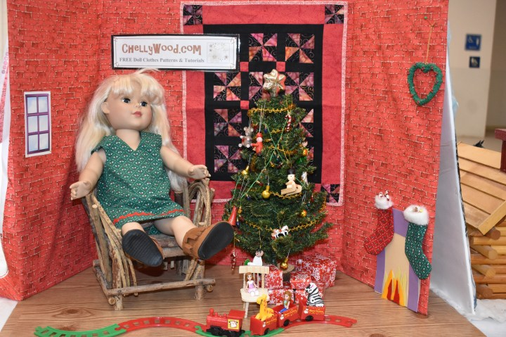 """The image shows an 18"""" Madame Alexander doll seated near a tiny quilt and a little doll-sized Christmas tree. In front of her is a choo-choo train for dolls, a fireplace framed with stockings, and a heart-shaped wreath; behind her is a sign that advertises the website ChellyWood.com, where you can download free, printable sewing patterns for dolls of many shapes and sizes."""