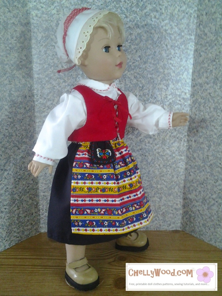 "Here we see an image of an 18 inch Madame Alexander doll wearing a traditional Swedish costume. Around her waist is a felt, hand-embroidered ""pocket,"" a type of purse or bag worn around the waist. The image is watermarked with the website where you can download free printable PDF sewing patterns for making this 18 inch doll outfit, including the pocket: ChellyWood.com"