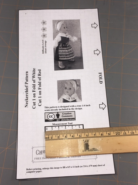 "The image shows a ruler held up against the ""measurement tool"" on a Chelly Wood pattern for making a doll's neckerchief."