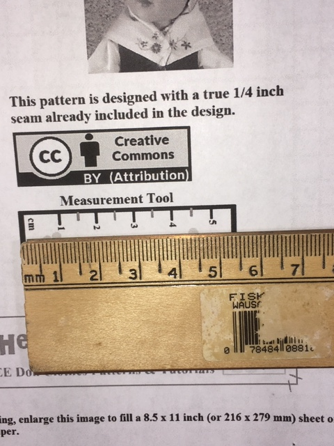 "The image shows a ruler held up against the ""measurement tool"" on a Chelly Wood pattern for making a doll's neckerchief. This is a close-up image, showing that the ruler's metric marks match the measurement tool on the printed pattern's measurement tool."