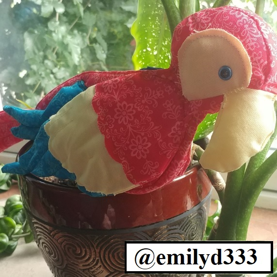 The image shows a zipper pouch parrot, designed by Emily D at CriticalHitDesigns on Etsy.