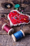 The image, which is purely decorative, shows a heart-shaped pincushion with needles and pins in it. Beside this are two spools of thread.