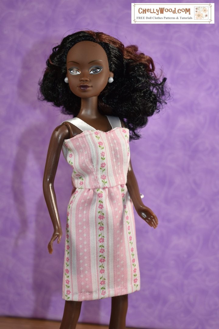 """This image shows a Queens of Africa doll wearing a pretty handmade dress made of thin pink material decorated with polka dots and flowers on pink and white striped fabric. The dress has a short, straight skirt and a summery bodice with straps made of ribbon. The watermark says, """"ChellyWood.com: Free doll clothes patterns and tutorials."""" The Queens of Africa dolls have a body shape similar to a Barbie-sized doll. She stands 11 inches high and has dark chocolate complexion. Her hair is quite curly. To purchase a Queens of Africa doll, go to https://queensofafricadolls.com/ In this image, we see the doll quite close-up, and the fabric fits her figure flatteringly."""