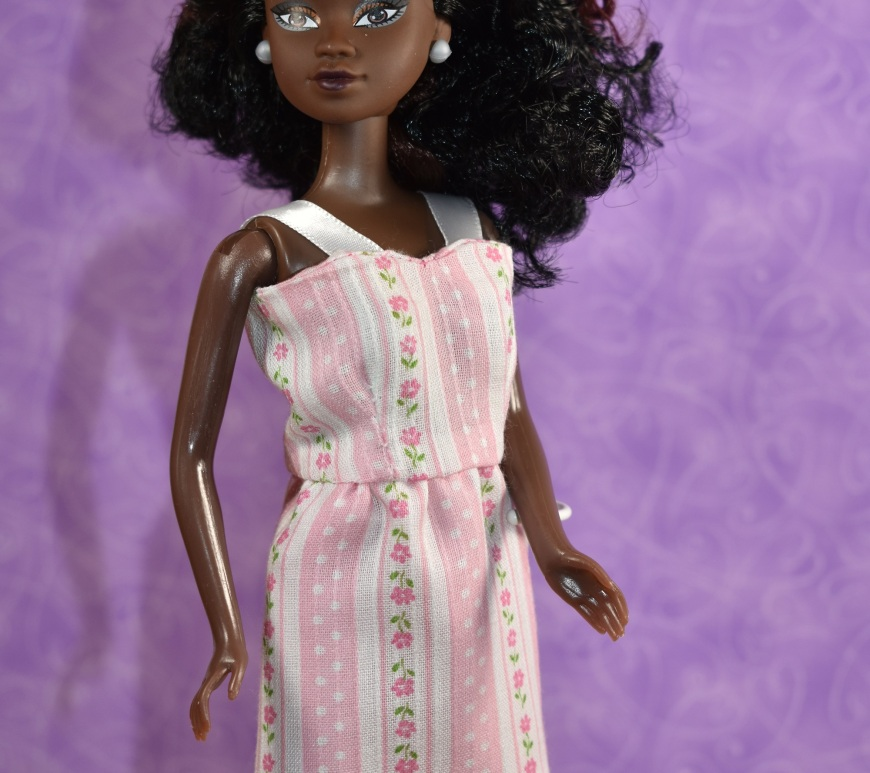 "This image shows a Queens of Africa doll wearing a pretty handmade dress made of thin pink material decorated with polka dots and flowers on pink and white striped fabric. The dress has a short, straight skirt and a summery bodice with straps made of ribbon. The watermark says, ""ChellyWood.com: Free doll clothes patterns and tutorials."" The Queens of Africa dolls have a body shape similar to a Barbie-sized doll. She stands 11 inches high and has dark chocolate complexion. Her hair is quite curly. To purchase a Queens of Africa doll, go to https://queensofafricadolls.com/ In this image, we see the doll quite close-up, and the fabric fits her figure flatteringly."