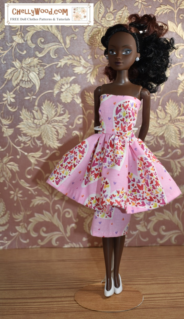 The image shows a Queens of Africa doll wearing a Valentine's Day dress. Her strapless dress fits 11-inch or 11.5-inch fashion dolls. The dress has a pencil skirt topped with a flouncy skirt. The fabric is pink with multi-colored hearts splattered across the fabric in random patterns. The watermark on this image tells you that ChellyWood.com offers free printable PDF sewing patterns and free tutorial videos.