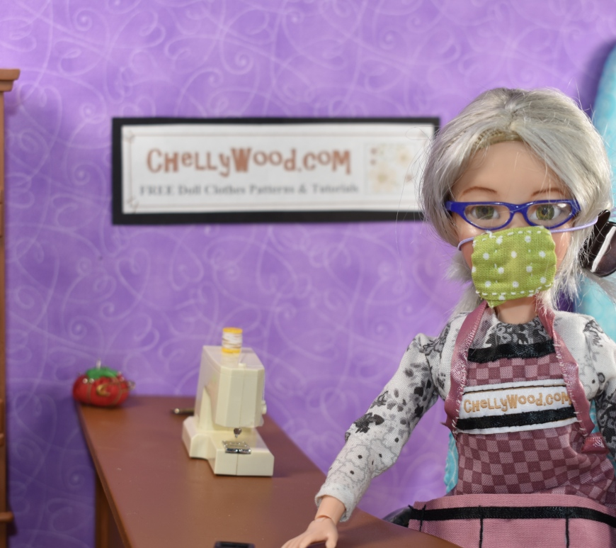 The image shows the doll representing Chelly Wood, the doll clothes designer, YouTuber, and blogger, wearing a hand-made cloth face mask. Behind her on the wall of her sewing room is the URL where you can download her free printable PDF sewing pattern for a child's cloth face mask, an adult's cloth face mask, and a cloth face mask to fit a 14 inch, 15 inch, 16 inch, or 17 inch doll: ChellyWood.com